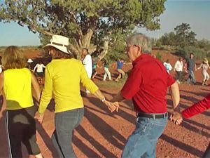 Ceremonial circle outdoors on Sedona red earth next to juniper tree. This represents working together to celebrate and to create positive change.