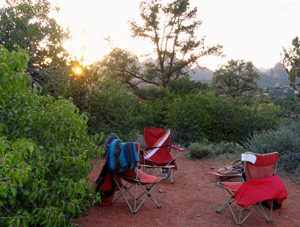 3 chairs in a circle of green trees outdoors in Sedona represents doing Sedona outdoor programs in nature with Crossing Worlds Journeys & Retreats