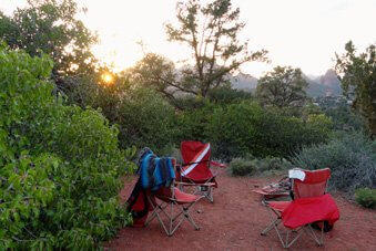 3 chairs on Sedona red earth surrounded by green shrubs. This represents the feeling of doing a Sedona outdoor seminar or circle.