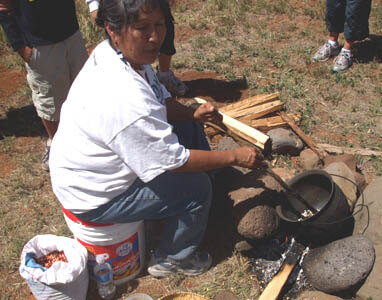 Hopi woman is stirring corn kernels in kettle over open fire making traditional parched corn.