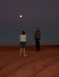 2 women on red rocks under the full moon connecting with nature at night.