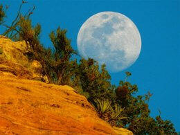 Full moon rising over red cliffs inspires connection with the moon and joyful circle of celestial connection