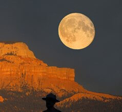 Full moon rising over Secona ref cliff with person in hat watching symbolizes our solo vision circle with the support of power animals.