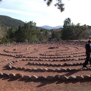 Large 11-path labyrinth with person walking it represents a group ceremony site used by Crossing Worlds Journeys.