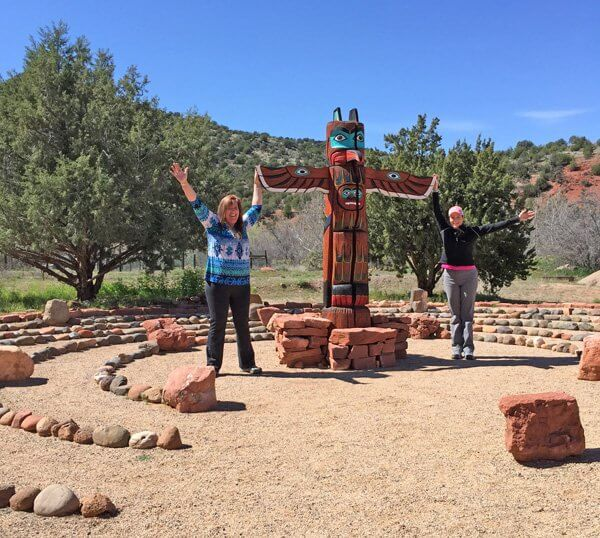 Ceremonial site with 4 concentric circles and a totem pole and 2 guests with arms upraised in center. This is a ceremony site ceremony near Oak Creek used for Ceremonial training and to teach timeless principles of ceremony.