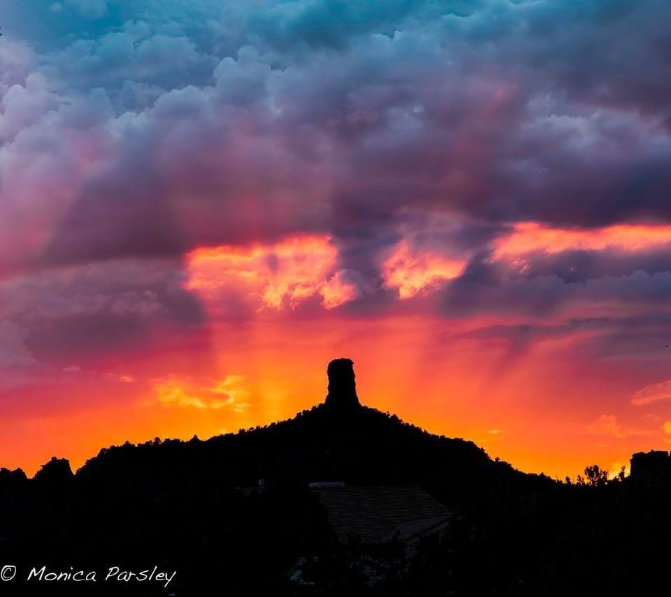 Rays of light from setting sun, sky colors of intense reds and purples with rain clouds above convey a feeling of the Spirit of Sedona.