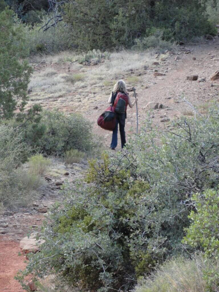 A single person with pack hiking in nature illustrates heading out on a solo overnight vision quest ceremony in nature