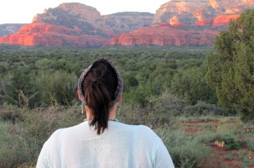 Woman facing the Sedona red cliffs at sunset. This is an earth-spirit circle to tune into the earth at a seasonal turning point, and sense sunset energies.