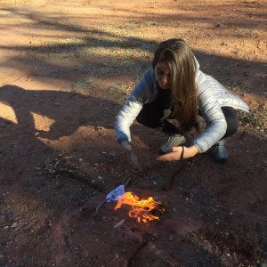 Photo of a woman kneeling with her hands above a small fire. This symbolizes the use of ceremony during a Sedona spiritual retreat to activate positive change..