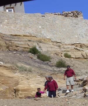 Hopi ancestor cliff trail below a village with 2 men walking with Hopi woman guide and child.