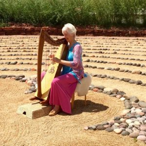 Large labyrinth with woman play harp in center means personalized Sedona ceremonies with harp music can be created to honor, bless, begin something new.