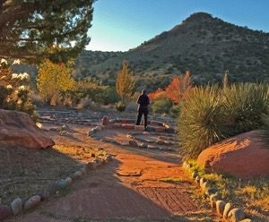Woman walking in ceremony in a labyrinth at sunset with fall colors on shrubs and a lava cone in background illustrates using ceremony to activate your new inspirations.