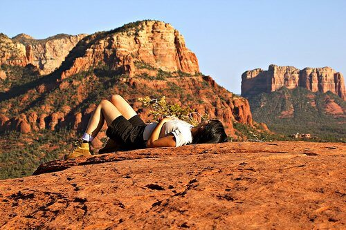 Woman laying on back on Sedona red cliff shelf. Signifies nature connection skills that are part of mystic vision, vision quest and shamanic practice.