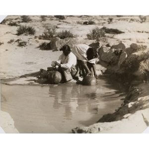Historic photo of Hopi women filling water jugs. Hopis believe all waters are sacred and that humankind is a participant in water-life.