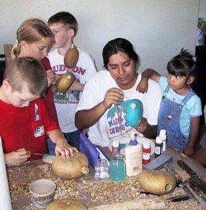 Hopi artist helping visitors make a gourd rattle during a Hopi journey.