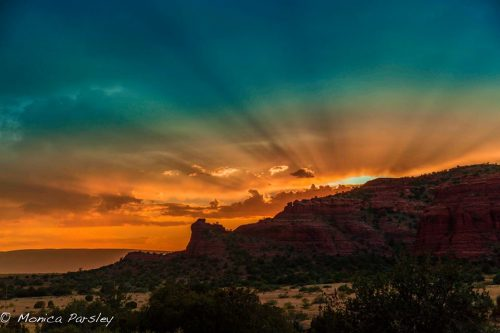 Sedona sunset photo with rays of sun going up into sky. Symbolizes Sedona as a place of mystic vision connection.