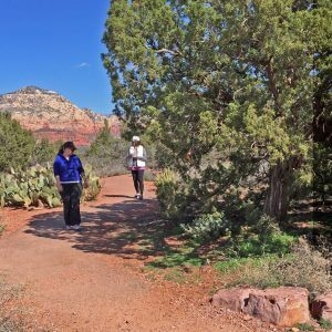 2 women walking in a focused way on red rock trail practicing nature connection at a discover Sedona outdoor program in nature