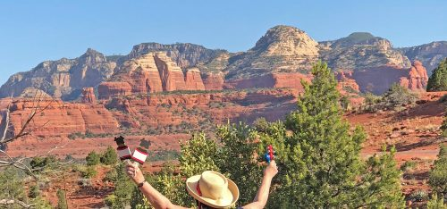 A woman with ceremonial items in uplifted hands as she faces red cliffs symbolizes our Sedona Fall Equinox Celebration, Ceremony and Mystic Vision program